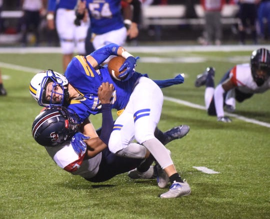 Mountain Home's Logen Walker attempts to break a tackle by a Marion defender on Friday night.