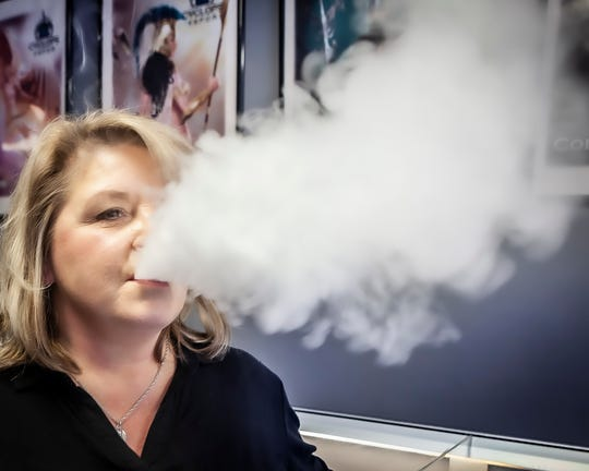 Stacey Hamilton, owner of Kaleidoscope Vapor in Murfreesboro and board member of the Vapor Technology Association, demonstrates what the water vapor that is emitted from e-cigarettes looks like.