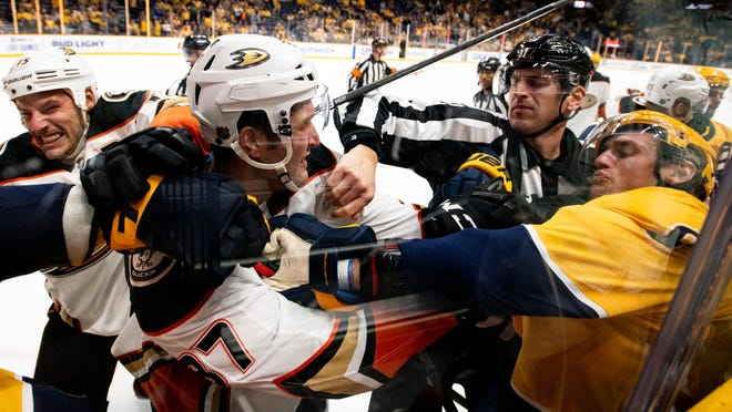 Linesman Bevan Mills tries to breakup a fight between Anaheim Ducks left wing Nick Ritchie (37) and Nashville Predators center Kyle Turris (8) during the third period at Bridgestone Arena in Nashville, Tenn., Tuesday, Oct. 22, 2019.