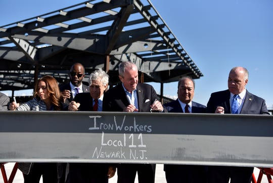 NJ Gov. Phil Murphy, center, Rick Cotton executive director of The Port Authority of New York and New Jersey, to governor's left, and Kevin O'Toole, chairman of the Port Authority, to governor's right, and other dignitaries, sign the final steel beam to be placed during construction of a new Terminal One at Newark Liberty International Airport on October 23, 2019.