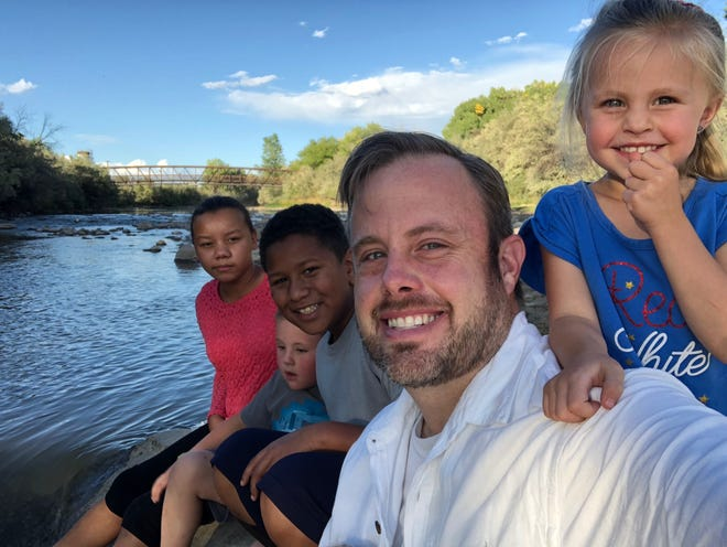 Sheldon Pickering poses with his children on the Animas River in Farmington this summer.