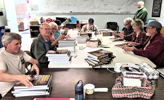 Signing copies of their book about the exploration of Fort Stanton Cave are from left,  John Lyles,  Ron Lipinski, Pete Lindsley, John McLean, Lee Skinner, John Corcoran, (standing Wayne Walker), Lynda Sánchez and Steve Peerman.