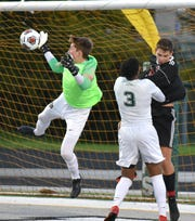 Novi goalie Ryan Zotkovich knocks a shot on goal out of the air during the Wildcats' Oct. 22, 2019 playoff game against Grand Blanc High. Novi blanked their opponents 2-0 to move on in the playoffs.