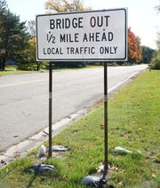 A sign leading up to the Lilley Road bridge near Michigan Ave. Work continues on its replacement.