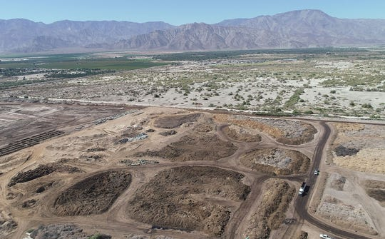 Large piles of green waste are collected the Sun Valley Recycling and Soil Amendment Co. on the Torres Martinez Reservation in Thermal, Calif. in this aerial drone photograph, October 9, 2019.  Desert Mirage High School can be seen here in the distance on the upper right.