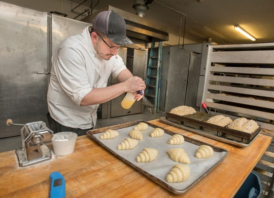 Coleman Jernigan sprays an egg wash on croissants before baking them at Emerald Coast Bread Co. on Wednesday.