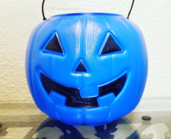 A blue plastic pumpkin or bucket signals that the child holding it has autism.