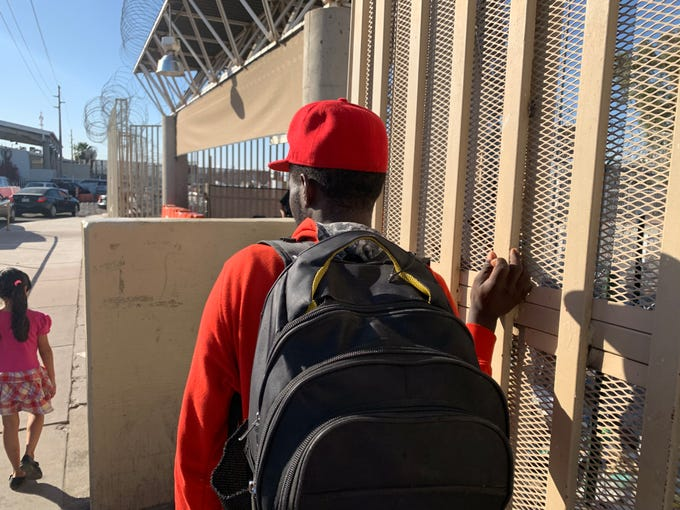 A Cameroonian migrant looks on as border residents make their way to the San Luis port of entry. He has waited in Mexico for three months to claim asylum in the U.S.