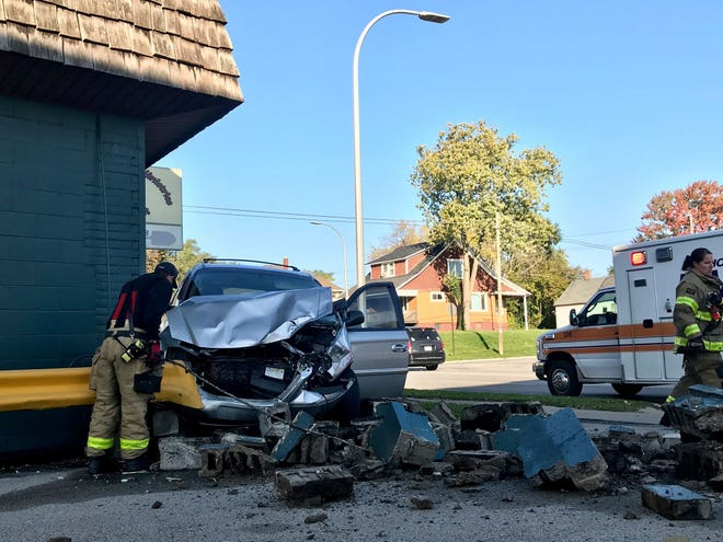 Port Huron Fire Department firefighters work on the scene of a crash where a vehicle hit a building at 1044 Lapeer Ave. in Port Huron.