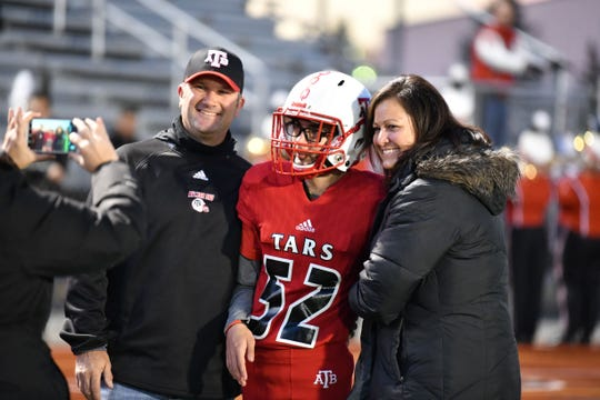 Anchor Bay senior Jeffery Cesta celebrates with his parents, Jeff and Paula, after he scored a touchdown during a senior night football game against Utica Stevenson on Friday, Oct. 18, 2019.