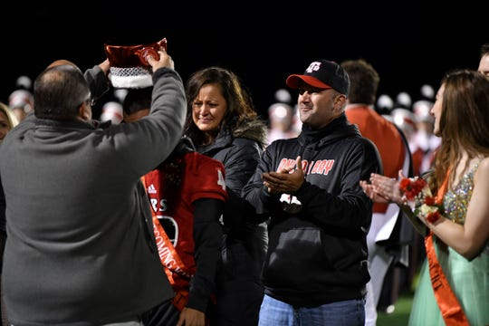 The parents of Anchor Bay senior Jeffery Cesta, Paula and Jeff, watch their son being crowned the homecoming king during a football game against Grosse Pointe South on Friday, Oct. 4, 2019.