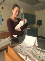 Kendra Sprenkle holds Lucas, a friend's baby whom she helped deliver as a doula. Her experience giving birth to her own child, Jade, inspired her to become a doula.
