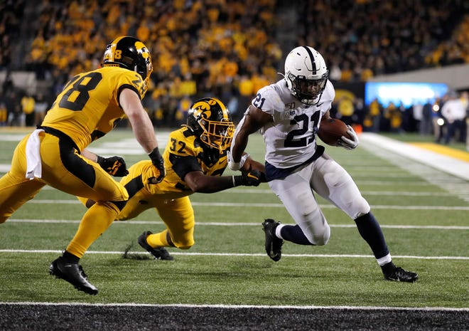 Iowa linebacker Djimon Colbert, left, loses his grasp of Penn State running back Noah Cain, right, as Cain runs in a touchdown during the second half of an NCAA college football game, Saturday, Oct. 12, 2019, in Iowa City, Iowa. (AP Photo/Matthew Putney)