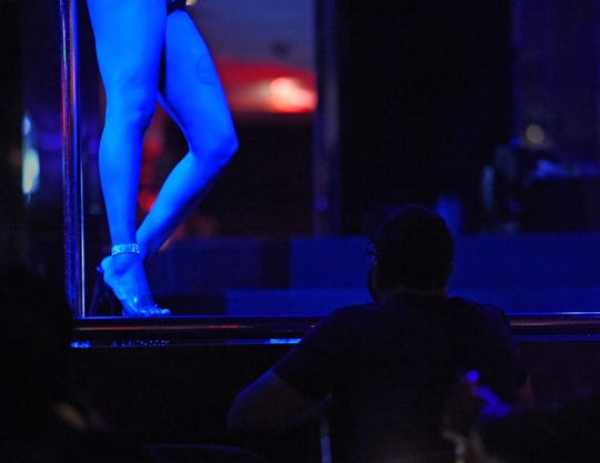 A customer watches a dancers perform on one of the states of the Wild Orchid Gentlemen's Club in Reno, Nevada on May 2, 2019.
