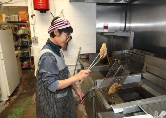Hyosook Lee makes fish fry at Mini H Mart on North Street.