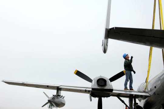 Jim Brown helps guide a crane as the Mohawk #926 aircraft is installed outside the Army Aviation Support Facility as public display in Salem on Oct. 23, 2019.