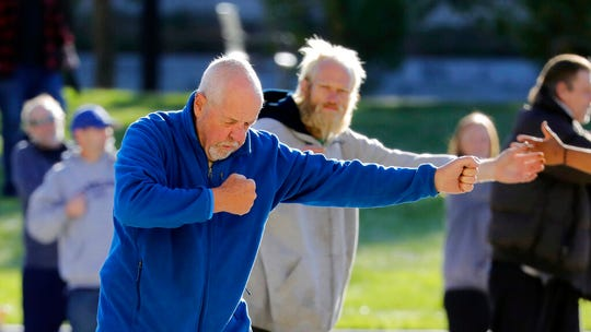 In this Oct. 7, 2019, photo, Bernie Hart, foreground, teaches tai chi in front of the Salt Lake Police headquarters, in Salt Lake City. The participants are homeless people who take part in a free tai chi program run by Bernie and his wife Marita, a retired couple who started the classes three years ago by knocking on tents and peering around grocery carts near the Salt Lake City Public Library to encourage people to join them. (AP Photo/Rick Bowmer)