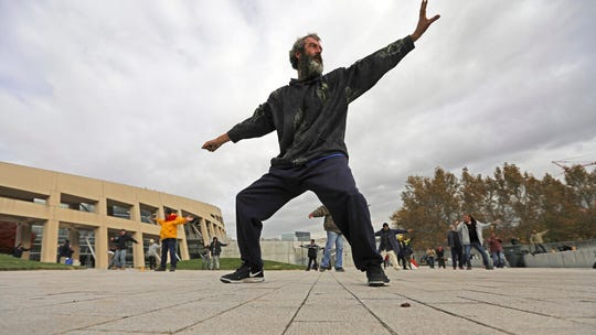 In this Oct. 2, 2019, photo, David Christopher Coons performs tai chi at the Salt Lake City Main Library, in Salt Lake City. The participants are homeless people who take part in a free tai chi program run by a retired couple who started the classes three years earlier. Coons was fired from his job as an electrician about five years ago. He has been homeless since, vacillating between sleeping in shelters or on the streets of Salt Lake City. (AP Photo/Rick Bowmer)