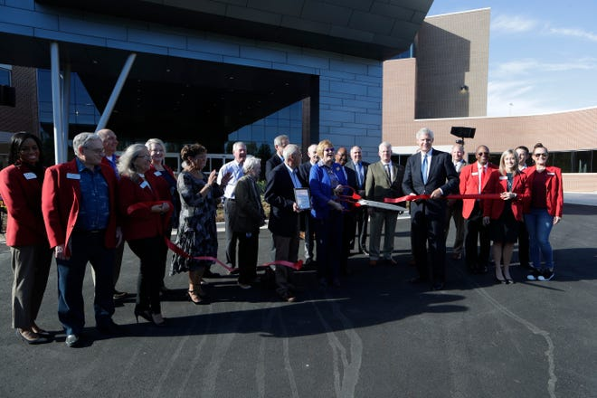 Polly White, senior vice president of clinical operations for Capital Health Plan, cuts the ribbon for CHP's new Metropolitan Center Wednesday, Oct. 23, 2019.