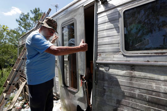 Charles Fincher, an Altha, Fla. resident, 75, removes the door to second trailer that he now lives in after Hurricane Michael destroyed his other trailer. Fincher held the door shut for hours as the storm raged on.