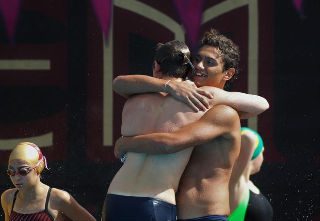 Maclay junior Dimitri Nakis hugs a teammate after a relay win during the District 1-1A swimming and diving meet at FSU's Morcom Aquatics Center on Tuesday, Oct. 22, 2019.