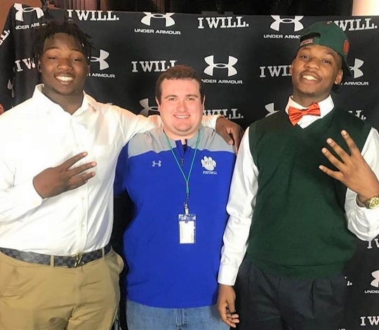 Jordan Wiggins assistant coach Ben James and Kamari Young celebrate their accomplishments on National Signing Day at Godby High School on Wednesday, Feb. 6, 2019. Wiggins signed with Georgia Southern and Young accepted an offer from FAMU.