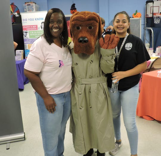 Thelma Washington, left, executive director of Gertrude Walden Child Care Center, McGruff the Crime Dog and Nayomie Duran of Explorer Post 878 of Stuart Police Department attend the East Stuart Community Health Fair at the 10th Street Complex on Oct. 12, 2019.
