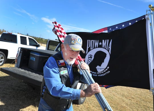 Vietnam Veteran Cliff Harney sets-up flags for a ceremony held to honor United States  Marine Corp. Vietnam Veteran Eddie Eugene McAnear, Wednesday afternoon.