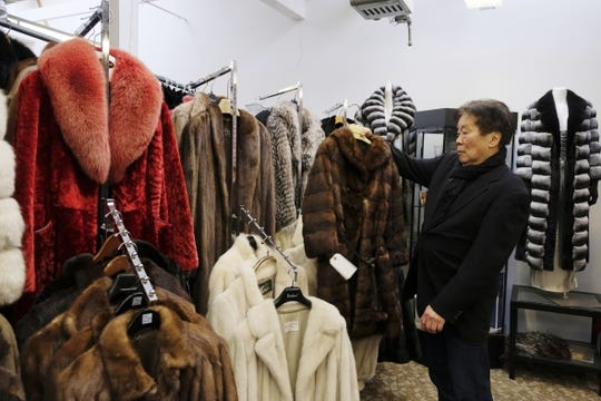 In this file photo taken Friday, March 16, 2018, Benjamin Lin holds up a fur coat at the B.B. Hawk showroom in San Francisco. At the time, San Francisco became the largest U.S. city to ban the sale of fur items in March 2018.