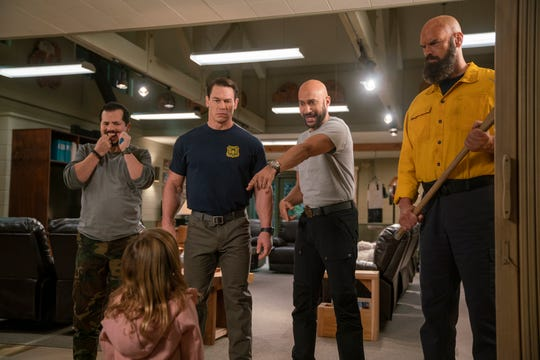 "A bunch of macho firefighters (from left, John Leguizamo, John Cena, Keegan-Michael Key and Tyler Mane) aren't sure what to do with a kid (Finley Rose Slater) in their midst in the family comedy ""Playing With Fire."""
