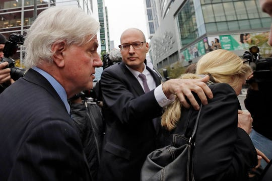 Gregory Abbott, far left, and his wife Marcia, far right, get into a car as they leave federal court after their sentencing in a nationwide college admissions bribery scandal, Tuesday, Oct. 8, 2019, in Boston.