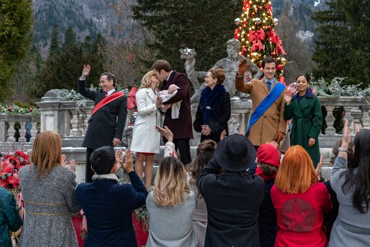 "The royal couple of Aldovia (Rose McIver and Ben Lamb, center) celebrate their child in Netflix's ""A Christmas Prince: The Royal Baby."""