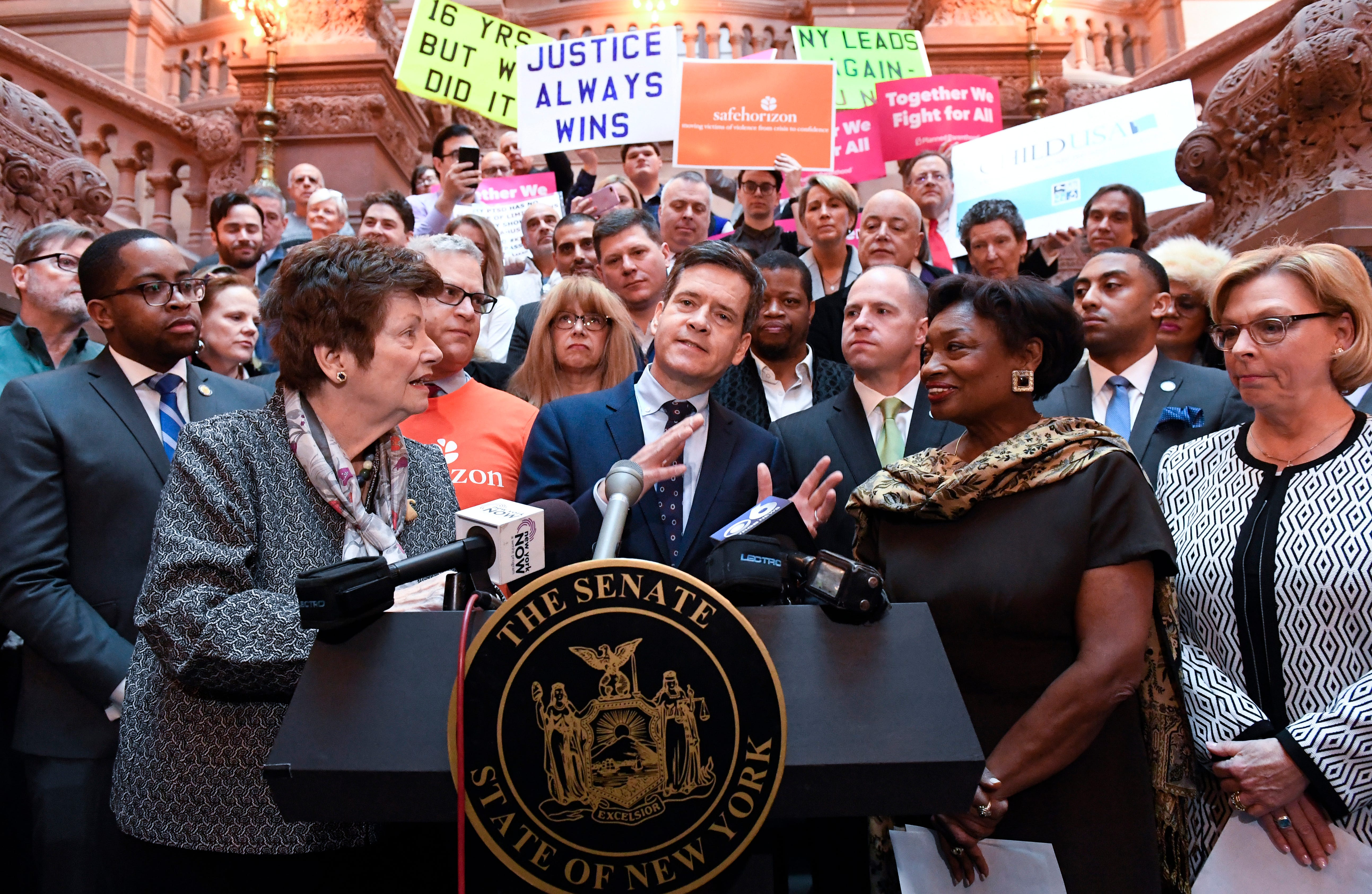New York Sen. Brad Hoylman, D-Manhattan, center, flanked by former Assemblywoman Margaret Markey, left, and Senate Majority Leader Andrea Stewart-Cousins, D-Yonkers, right, stands with survivors and advocates speaking in favor of passing legislation authorizing the Child Victims Act during a news conference at the state Capitol in Albany, New York, on Monday, Jan. 28, 2019.