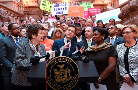 New York Sen. Brad Hoylman, D-Manhattan, center, flanked by former Assemblywoman Margaret Markey, left, and Senate Majority Leader, Andrea Stewart-Cousins, D-Yonkers, right, stands with survivors and advocates speaking in favor of passing legislation authorizing the Child Victims Act during a news conference at the state Capitol in Albany, N.Y., on Monday, Jan. 28, 2019.