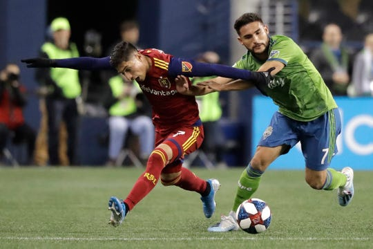 Seattle Sounders midfielder Cristian Roldan, right, fends off Real Salt Lake forward Jefferson Savarino during the first half of an MLS Western Conference semifinal playoff soccer match Wednesday, Oct. 23, 2019, in Seattle.