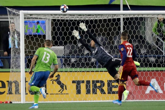 Real Salt Lake goalkeeper Nick Rimando, center, leaps as a shot goes wide and Seattle Sounders forward Jordan Morris, left, and Real Salt Lake defender Aaron Herrera, right, watch during the first half of an MLS Western Conference semifinal playoff soccer match Wednesday, Oct. 23, 2019, in Seattle.