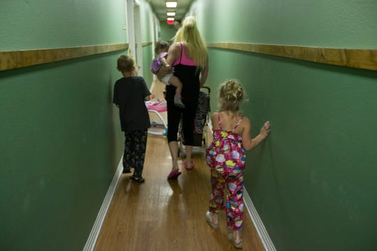 A women and her children walk through the halls in the residential area of the Women's Shelter of South Texas on their way to bed in June 2015. The family must stay together at all times in the shelter and children under the age of 13 have to be in bed by 8 p.m.