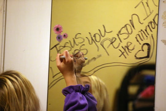 "A girl traces the words ""Jesus loves you person in the mirror"" in the bedroom she shares with her family and another family at the Women's Shelter of South Texas in June 2015."