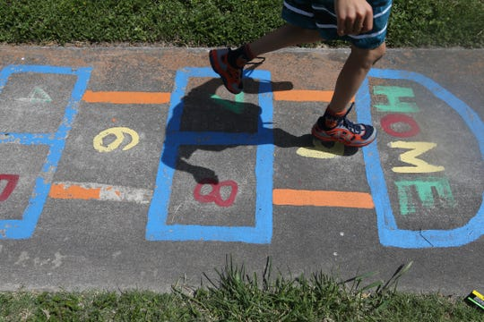 A boy plays hopscotch at a park in June 2015. His mother, who is staying at the Women's Shelter of South Texas, tries to keep her children active.