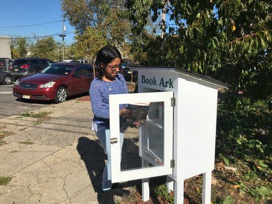 Nataly Alanis Colin, 10, places books into a Book Ark at 3rd and Erie streets in North Camden. The Gloucester City fifth grader takes care of another book ark near her home.