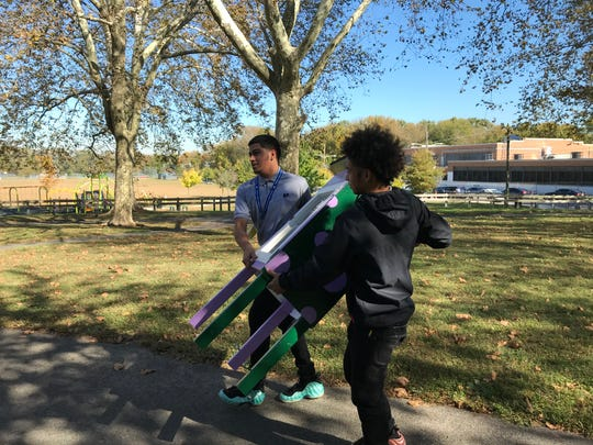 Frank Mass (left) and Damien Figueroa, both 16, carry a book ark across Pyne Poynt Park, where it will hold books for all ages, free for the taking. They were part of a contingent of Mastery Pyne Poynt High School students helping with the book ark's installation.