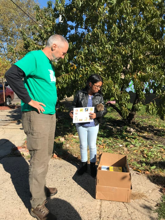 Tom Martin and Nataly Alanis Colin consider a box of donated books for the Book Arks they installed in North Camden.