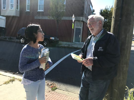 Nataly Alanis Colin talks with John Martin at 3rd and Erie streets in North Camden. Martin, who practiced dentistry in Westmont for 40 years, builds the book arks.
