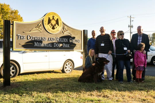 The Corzine family poses with the new sign for the Catherine and Holden Corzine Memorial Dog Park which was officially dedicated on Wednesday, Oct. 23.