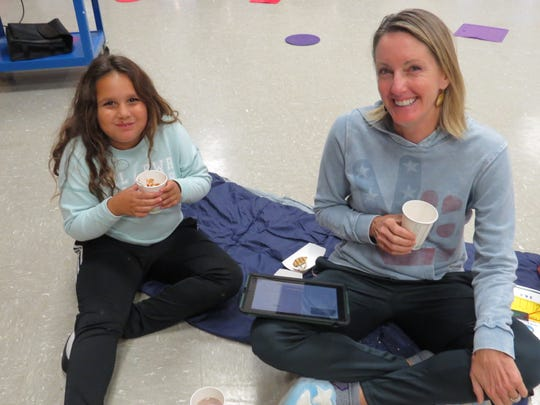 Bonnie Nolan of Colonia enjoys refreshments while reading with her daughter, Olivia Nolan