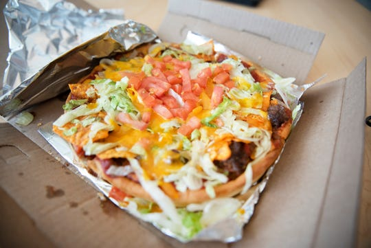 Felix & Oscar's Taco pizza: Seasoned ground beef, chips, lettuce, cheddar cheese & tomatoes. $21.13 including delivery. Roughly one-hour delivery.