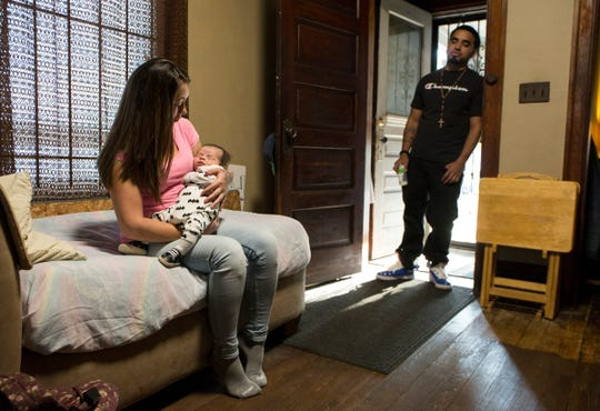 Jessica Hinojosa, 32, with infant son Johny Saucillo, relaxes with her fiance, John Saucillo, 26, where they live with family in southwest Detroit, Wednesday, Oct. 9, 2019.