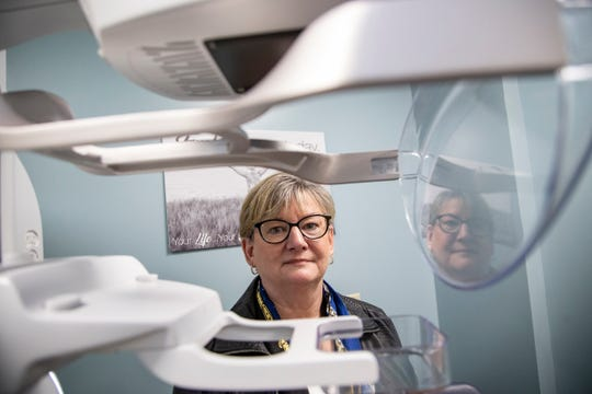 Margaret Rhead stands for a photo next to a 3D mammography machine at McKenzie Health System in Sandusky Wednesday, Oct. 16, 2019. Rhead had 10 routine mammograms, but they came back inconclusive, and she wasn't willing to accept that result as meaning she was cancer free.