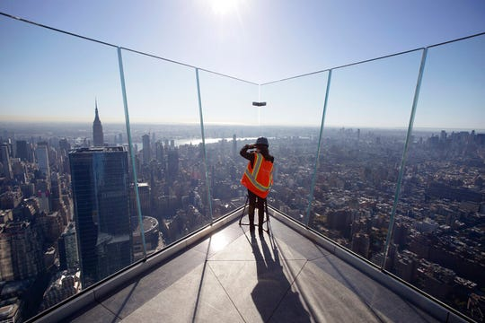 "A videographer works on ""Edge,"" an outdoor observation deck overlooking New York."