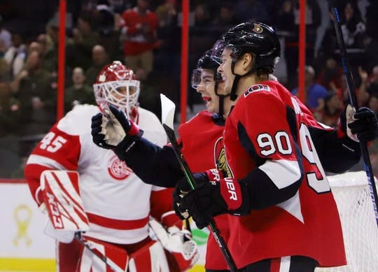 Senators center Jean-Gabriel Pageau celebrates his goal with teammate Vladislav Namestnikov (90) as Red Wings goaltender Jonathan Bernier (45) stands nearby during the second period on Wednesday.